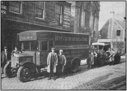 Photo of Stevenson's shop & delivery vans in Bruce Street with founder William and son, Ian Stevenson (left) and van driver in forefront with other staff behind. c. 1928