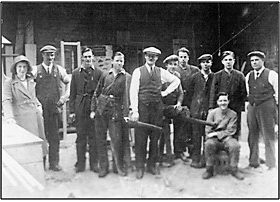Photo C. 1930 – John Jackson (centre) with sons John Jnr. & William (3rd & 4th from left), daughter Margaret (left) and other members of staff, probably at Mill Street.