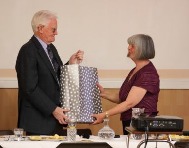 Photo of George Robertson receiving his presentation from Carolyn Thompson