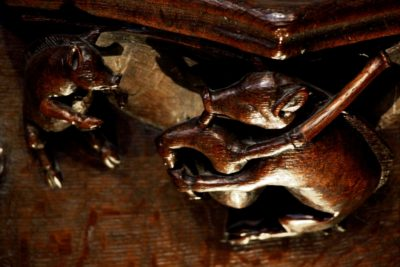 Photo of carvings of a pig playing the bagpipes on the misericords