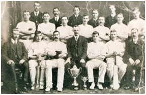 Photo of the Elgin Rubberwork's Cricket Team c.1925 with factory manager, Sandy Howie 3rd from left in the front row with members of the Stewart family in suits in front row