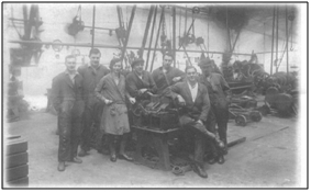Photo of Tod's Workshop c.1938 with Rennie Tod and Stuart Bowman (2nd and 4th from the left). In the background to the right can be seen the flywheel of the oil engine used to drive the overhead pulley system.